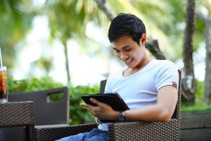 man smiling sitting in chair using tablet device