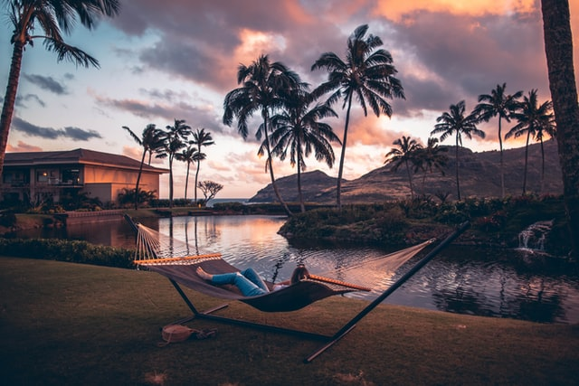 woman relaxing in hammock on beach at sunset near palm trees