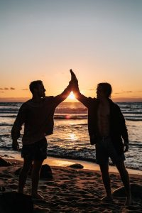 Two friends giving high fives on beach at sunset, no longer stressed out in Oregon. You can get help for stress in hillsboro, or and online therapy in Oregon at Life Discovery Counseling on the eastside and westside. Get christian anxiety counseling in clackamas, or
