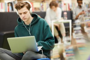 Serious hipster student boy listening to music in headphones and using laptop for video therapy in Oregon with a caring, Christian counselor in Portland, OR. Contact us to start Online therapy in Oregon today.