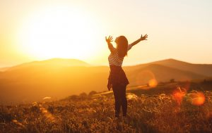 Happy woman jumping and enjoying life in field at sunset in mountains with hands outstretched. You can get christian depression treatment in Clackamas, OR and Hillsboro, OR to feel more joy in your life too. Get online therapy for depression in oregon here.