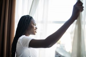 Morning of beautiful young woman opening curtains in bedroom thinking about the signs of codependency and enmeshment | coping with codependency counseling in Happy Valley, Damascus, Clackamas and Hillsboro, OR at Life Discovery Christian Counseling