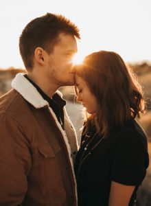 Man giving woman a kiss on the forehead after doing online therapy in Oregon to talk about the signs of codependency and enmeshment | coping with codependency counseling in Happy Valley, Damascus, Clackamas and Hillsboro, OR at Life Discovery Christian Counseling