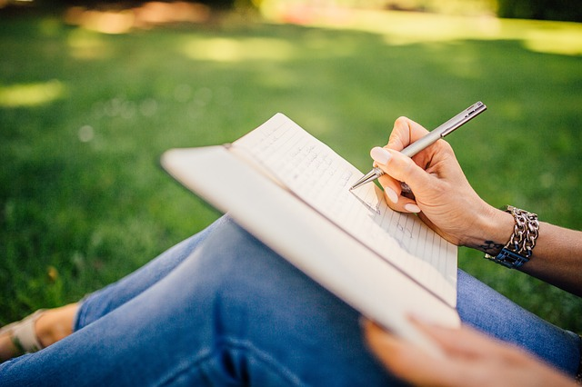 Woman writing her thoughts in a journal outside in the sun. She needs christian trauma therapy in Clackamas, OR and Hillsboro, OR with online christian counseling and christian marriage counseling for her relationship.