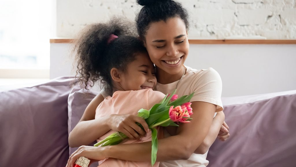 African mom hugs daughter express gratitude for attention and flowers from her daughter. She is practicing mindfulness and staying present with her family after Christian counseling in Clackamas, OR and Hillsboro, OR with video therapy in Oregon.
