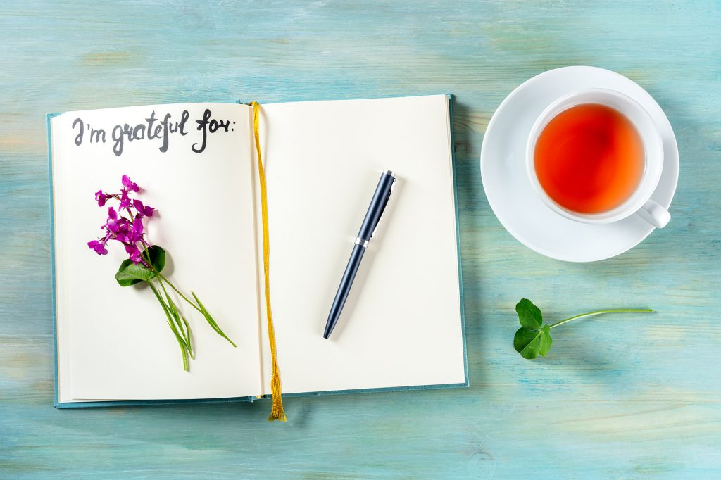 Gratitude journal with a pen and a cup of tea, with the handwritten phrase I am grateful for and a flower. This is one way to practice gratitude in Oregon. You can also get help for anxiety, depression and stress with Christian counseling in Clackamas, OR and Hillsboro, OR here.