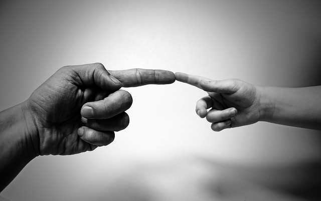 People touching fingers, an adult and a child in a grayscale photo. You can get support for anxiety, depression and stress with a Christian Counselor in Clackamas, OR here or with online therapy in Oregon.