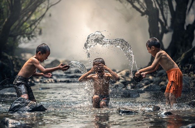 Photo of children playing in a creek and splashing each other. This represents the you you can feel when you wait for God to bring about real change. Learn more from a christian therapist who offers christian counseling in Oregon and online therapy in Oregon