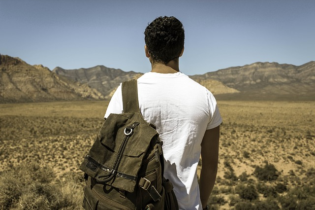 Man walking through a field toward mountains with a backpack. Carrying the weight of pain can cause mental health concerns like anxiety and depression. Talk with a Christian Counselor in Clackamas, OR or a christian therapist in Hillsboro, OR in online therapy in Oregon.