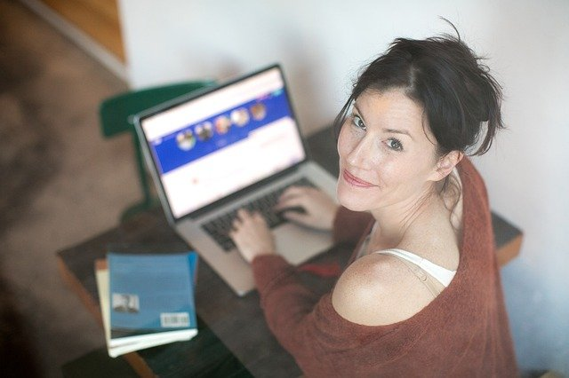 Woman looks up at the camera while typing on the computer, with a smile. You can feel free and confident with online therapy in Oregon. Christian counselors in Clackamas, OR can help you thrive after anxiety treatment.
