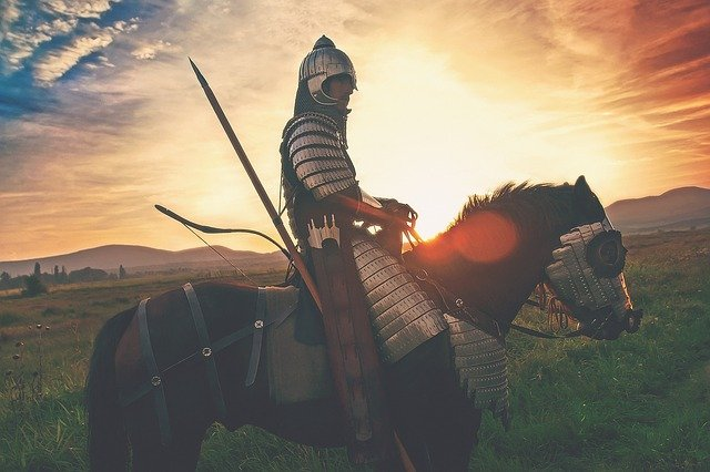 Knight on a horse with full armor in the sunset on a field. Anxiety and depression can make you don a mask that a skilled Christian counselor in Hillsboro, OR or a Christian therapist in Clackamas, OR can help with. Anxiety treatment with christian counseling in online therapy in Oregon can help.