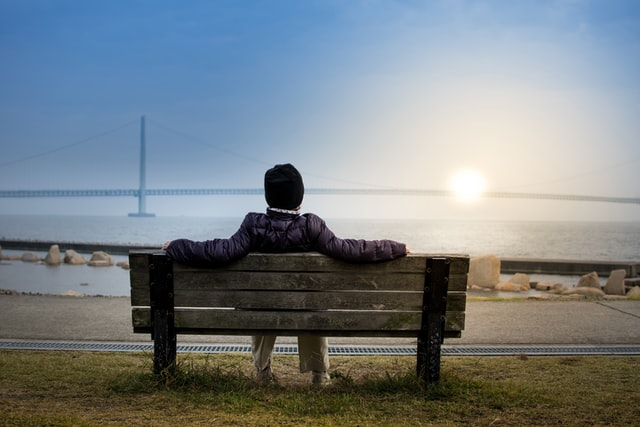 Person sitting on bench looking at sunset. Online counseling in Oregon with a skilled Christian therapist in Clackamas, OR can help. Get help for worry and stress in Hillsboro, OR here from a Christian counselor.